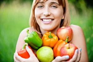 smiling woman with capsicums and apples