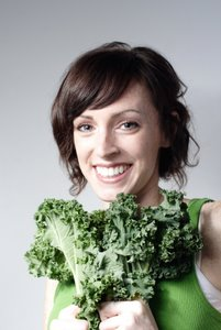 smiling woman holding kale leaves