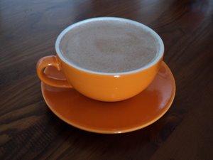 raw coffee in orange cup